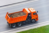 Orange truck dump with a load of soil in the body rides on the highway.