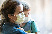 Mature woman posing with her son, both with protective masks, very sad looking through window worried about Covid-19 pandemic