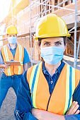 Mature female construction worker looking at the camera wearing a protective face mask
