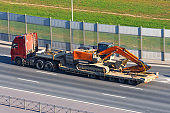 Heavy new yellow excavator on transportation truck with long trailer platform on the highway in the city.