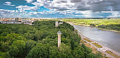 Beautiful view of the public city park with a green area and a lighthouse on the river