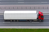 Truck with a white container on a trailer rides on a city highway, aerial side view.