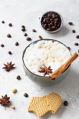 Cup of black coffee or cappuccino with milk foam decorated with anise star and cinnamon stick on light grey table with gingerbread cookies and roasted coffee beans. Lifestyle and coffee concept.