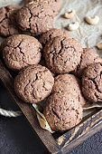 Chocolate cookies with nuts on a brown wooden tray. An old brown concrete background. Copy space for text.