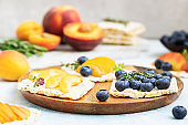 Mini rice cakes with blueberries, apricots, nectarines and cream cheese with honey for healthy breakfast. Light blue concrete background. Summer dieting sandwiches.