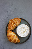 Cup of cappuccino coffee and two fresh croissants on grey stone table. French breakfast. Top view, copy space.