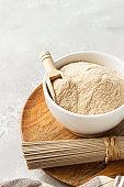 Buckwheat flour in bowl, small wooden scoop with flour and dried soba noodles. Healthy diet, gluten free products.
