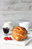 Delicious breakfast with fresh croissants and berries with cup of coffee on a light grey background.
