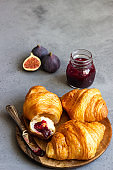 Fresh butter croissants on wooden plate on grey concrete background.