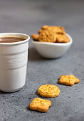 Cup of coffee with sweet mini cookies on grey concrete background. Free space for text.