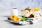 Sliced no bake apricot cheesecake garnish with chocolate glaze, fresh apricots and mint, light stone background. Delicious summer dessert.