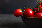 Fresh ripe cherry tomatoes and basil on a wooden background.