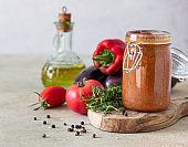 Vegetable caviar in jar, fresh eggplants, bell pepper, tomatoes and thyme on wooden board. Homemade preserves. Vegetarian cuisine. Autumn harvest.