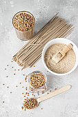 Organic uncooked buckwheat grains in glasses, buckwheat flour in a bowl and dried buckwheat soba noodles, light grey concrete background. Healthy concept.