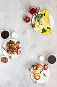 Breakfast menu food frame with a copy space. Belgian waffles, cottage cheese pancakes, omelette, chocolate sauce, berries, coffee, milk and orange juice.