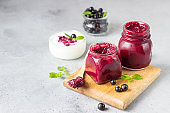 Jar of delicious homemade black currant curd, custard or jam with natural yogurt and fresh berries on grey background. Healthy breakfast.