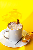 Autumn coffee or cappuccino composition. White coffee cup with milk foam, cinnamon stick and autumn leaves on yellow background. Fall hot drinks, cafe and bar concept. Bright sunlight and shadows.