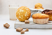 Vanilla muffins and muffins with streusel in paper cups with a glass of milk. Breakfast or snack for children.
