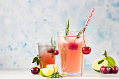 Cocktail or lemonade with cherries, lime and rosemary on a grey concrete table. Summer refreshment drink.
