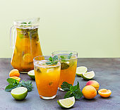 Delicious refreshing drink with apricot, lime and mint in jug and glasses on green background.