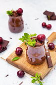 Chocolate mousse with mint and sweet cherry in portion glasses on wooden cutting board. Light blue concrete background.
