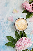 Morning cup of coffee and a beautiful peonies flowers on blue concrete background, top view. Cozy breakfast. Flat lay.