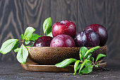 Ripe juicy purple plums with drops in wooden bowl with leaves, dark brown concrete background.