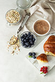 Croissant with fresh berries, muesli and a cup of coffee or hot chocolate on a light background. Copy space.