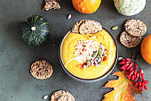 Roasted thick pumpkin vegetarian cream soup with pumpkin seeds, multigrain crackers and seeds on green stone background. Top view.