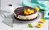 Cream mousse cake or no baked cheesecake with apricot decorated with chocolate glaze, fresh apricots and mint on light background.