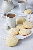 Plate with homemade coconut cookies and a cup of coffee with milk on a light background.