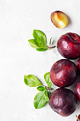 Ripe juicy purple plums, whole and slices, with leaves. Light grey stone background. Healthy vegetarian food.