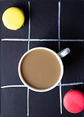 Cup of coffee with colorful french macarons.
