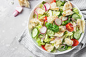 Vegetarian fattoush salad. Traditional Middle Eastern salad with toasted pita bread and vegetables. Lebanese cuisine. Light grey stone background.
