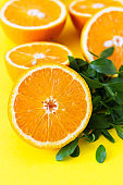 Fresh orange citrus fruit with leaves on yellow paper background. Juicy and sweet fruit. Concentration of vitamin C.
