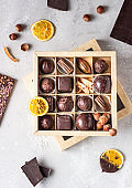 Assortment of sweet confectionery with chocolate candies and pralines on a light grey stone background.