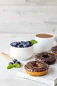 Breakfast concept: donuts with chocolate glaze, a cup of coffee, granola and fresh blueberries with mint on light gray background. Selective focus, copy space.