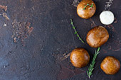 Portobello mushrooms, thyme and rosemary over dark brown concrete background.