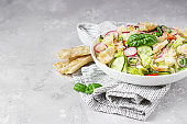 Delicious Fattoush or Arab salad with pita bread, fresh vegetables and basil on white plate. Middle Eastern bread salad.