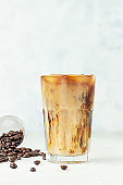 Iced coffee with milk in a tall glass with roasted coffee beans on light grey concrete background. Summer refreshment drink. Selective focus.