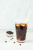 Espresso tonic, refreshment summer drink with tonic water, coffee and ice cubes, light grey concrete background. Trendy coffee drink.