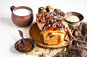 Apricot jam twisted loaf bread or babka with nuts and spices with a cup of milk. Homemade yeast bun babka.