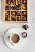 Coffee cup and assortment of fine chocolate candies on light grey stone background.