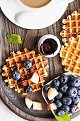 Belgian waffles with fresh blueberries, peaches, chocolate sauce and a cup of coffee. Liege style belgian waffles. Breakfast or lunch concept.