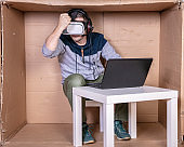 employee with virtual reality glasses working in his home cardboard office