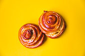 Two Cinnamon Buns on yellow background