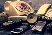 An old telephone with rotary dial, landline and obsoleted cellphone on a grunge background.