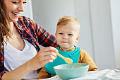 mother feeding baby food child eating family care childhood cute spoon