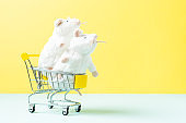 Two Soft toy pet white mouse in the shopping cart, the concept of a responsible approach to the purchase of pets. Yellow mint background with space for text.