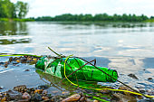 Glass bottle on the riverbank pollutes the environment. Nature pollution with garbage left by vacationers on the beach